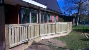 Bild på ny altan med staket och grind.